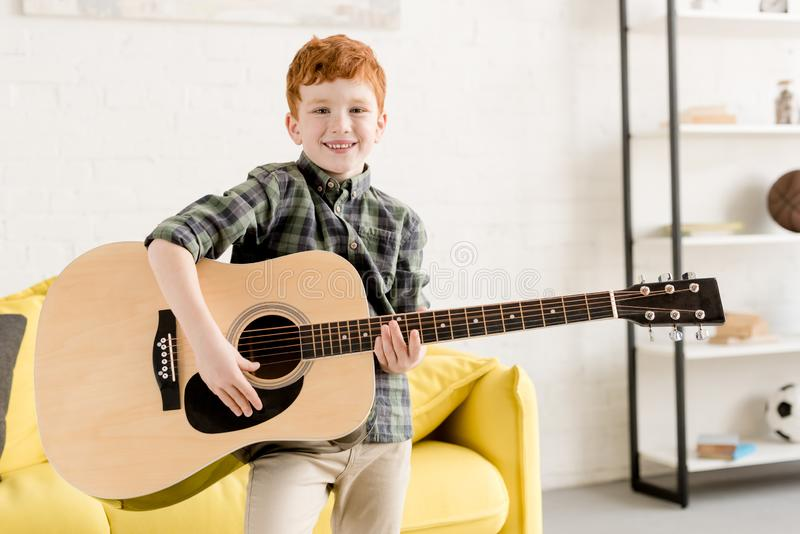 Cute little boy holding acoustic guitar and smiling. At camera stock photo