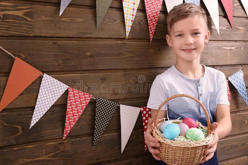 Cute little boy holding basket full of Easter eggs near wooden wall decorated with party pennants royalty free stock image