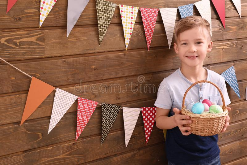 Cute little boy holding basket full of Easter eggs near wooden wall decorated with party pennants stock photos