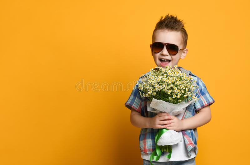 Cute little boy holding a bouquet of flowers. stock photography
