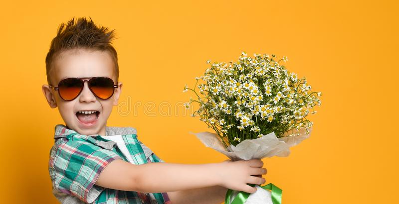 Cute little boy holding a bouquet of flowers. royalty free stock photos