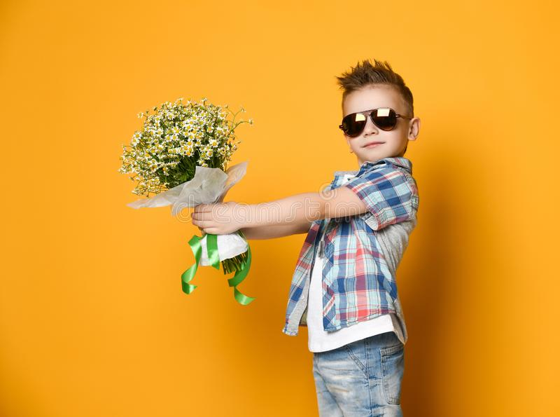 Cute little boy holding a bouquet of flowers. royalty free stock images