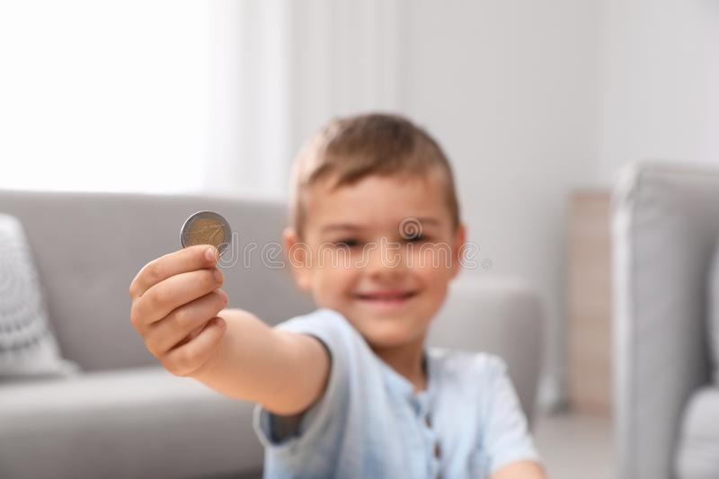 Cute little boy holding coin at home royalty free stock photo