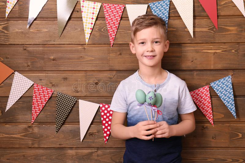 Cute little boy holding Easter eggs near wooden wall decorated with party pennants stock photo