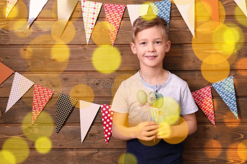 Cute little boy holding Easter eggs near wooden wall decorated with party pennants royalty free stock photography