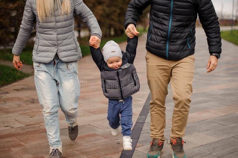 Cute little boy holding parents hands and jumping royalty free stock image