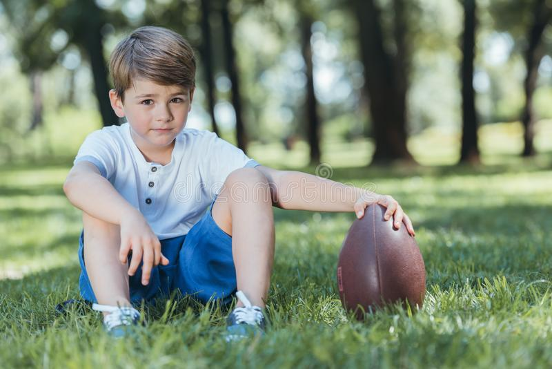 cute little boy holding rugby ball while sitting on grass and looking royalty free stock photos