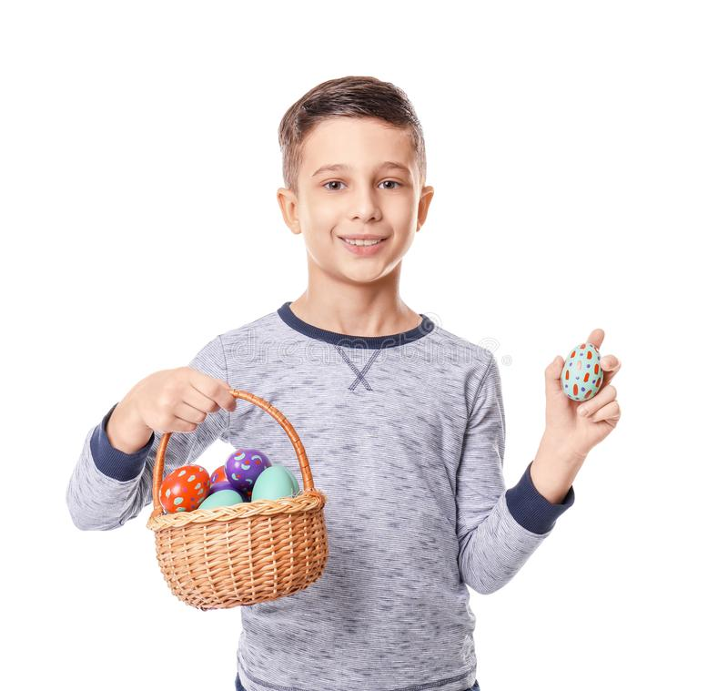 Cute little boy holding wicker basket with Easter eggs on white background stock photography