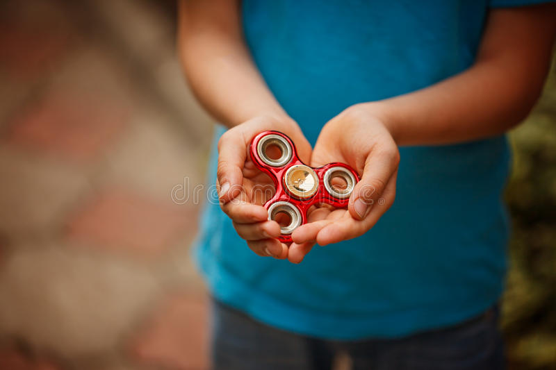 Cute little boy holds a spinner fidget in his hands. Trendy and popular toy for children and adult. stock image
