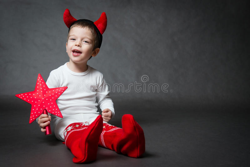 Cute little boy with horns. Cute little boy with devil horns and red star, gray background stock images