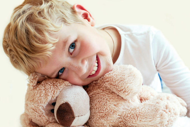 Cute little boy hugs his teddy bear. The manifestation of feelings: of tenderness and care stock images