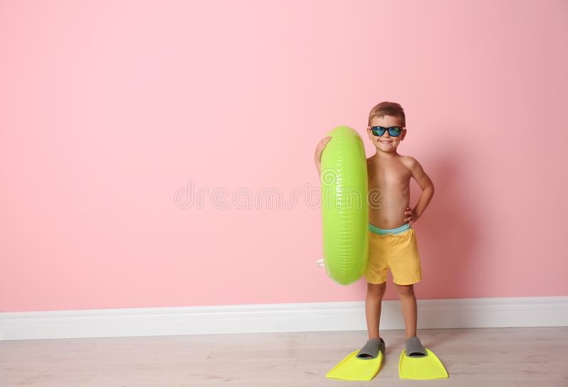 Cute little boy with inflatable ring wearing flippers color wall. Cute little boy with inflatable ring wearing flippers near color wall royalty free stock photography