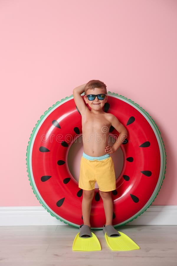 Cute little boy with inflatable ring wearing flippers. Near color wall stock photos