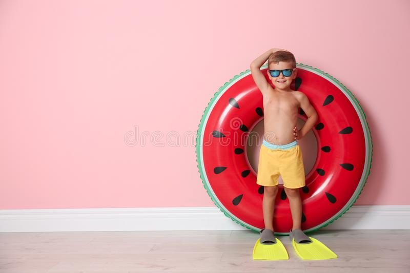 Cute little boy with inflatable ring wearing flippers. Near color wall royalty free stock image
