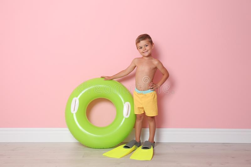 Cute little boy with inflatable ring wearing flippers. Near color wall royalty free stock photography