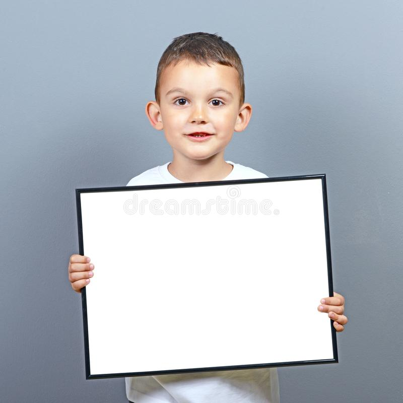 Cute little boy kid holding blank board with space for some text  against gray background royalty free stock images