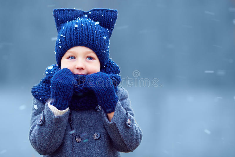 Cute little boy, kid in winter clothes walking under the snow stock photo