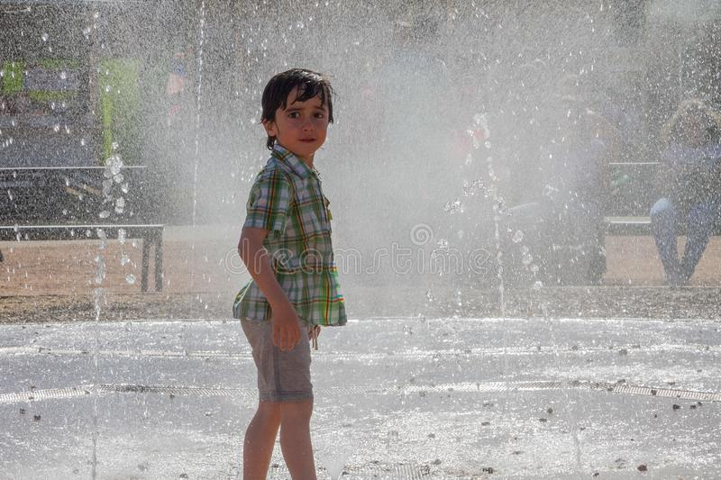 Cute little boy is laughing and having fun running under a water fountain stock photos