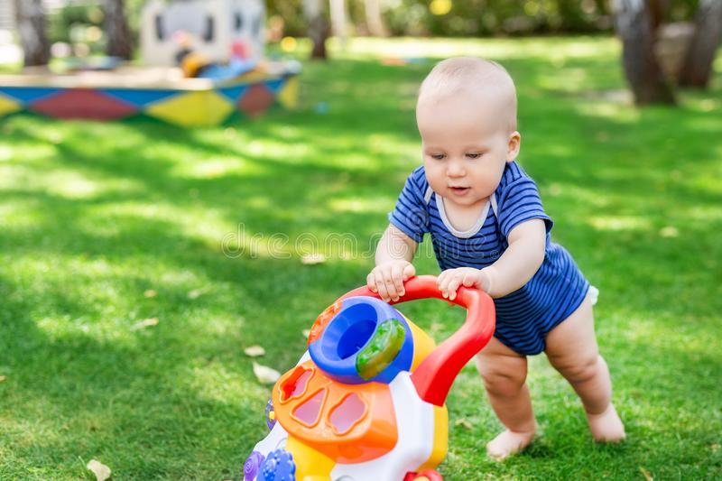 Cute little boy learning to walk with walker toy on green grass lawn at backyard. Baby laughing and having fun making first step a. T park on bright sunny day stock image
