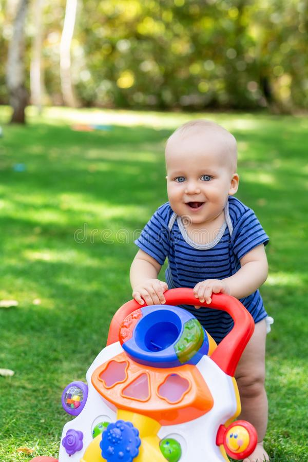 Cute little boy learning to walk with walker toy on green grass lawn at backyard. Baby laughing and having fun making first step a. T park on bright sunny day royalty free stock photo