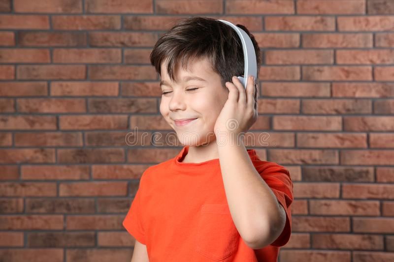 Cute little boy listening to music with headphones against wall stock photos