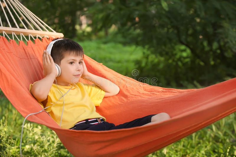 Cute little boy listening to music while relaxing in hammock on summer day stock photography