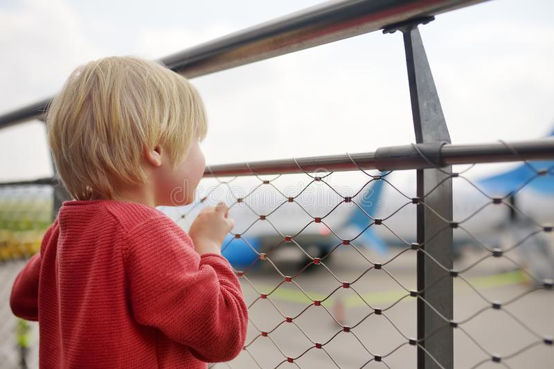 Cute little boy look at airplanes on observation deck at airport of small european town before flight. Charming kid passenger royalty free stock photography