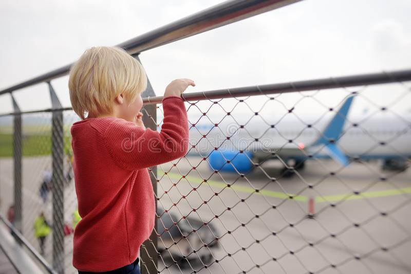 Cute little boy look at airplanes on observation deck at airport of small european town before flight. Charming kid passenger. Waiting boarding. Family travel stock photography