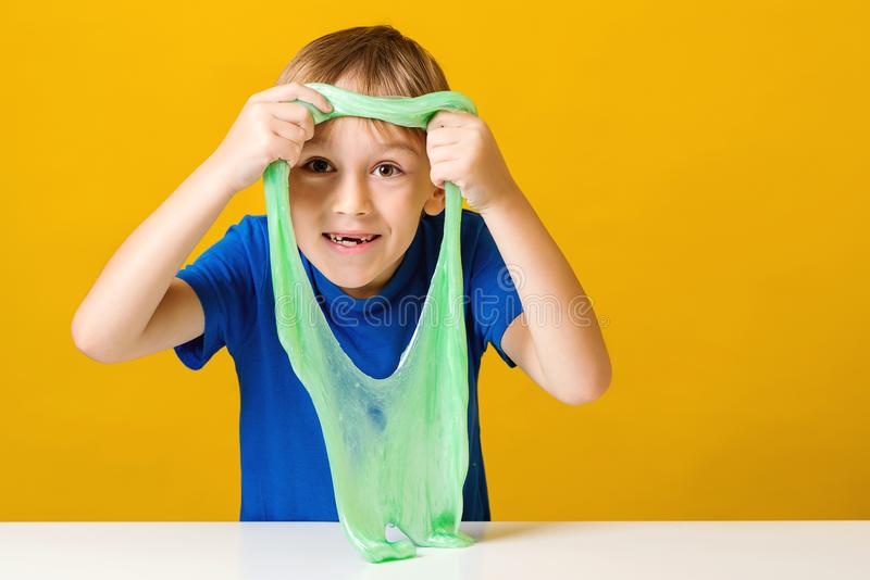 Cute little boy looking through hole in a slime. Happy kid plays with slime. Happy childhood. Trendy slime toy royalty free stock photo