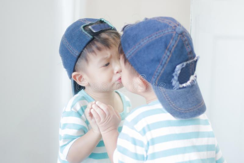 Cute little boy looking at mirror , kid self talk via mirror. Play with salt stock images