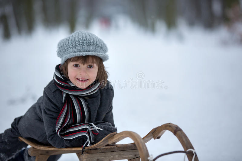Cute little boy, lying down on sledge, smiling at camera royalty free stock photography