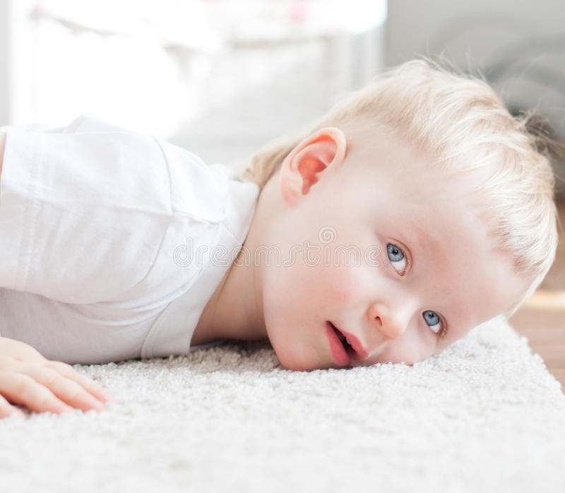 Cute little boy is lying on the carpet royalty free stock images