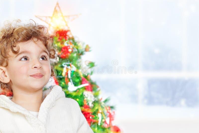 Cute little boy near Christmas tree royalty free stock image
