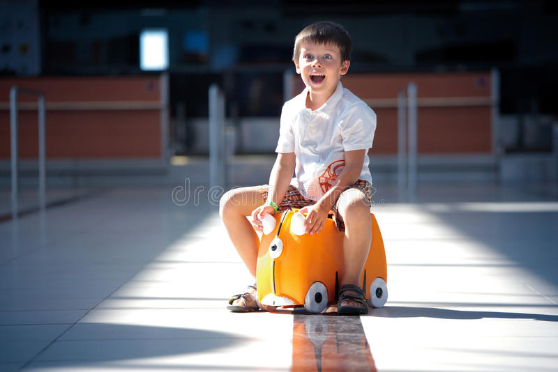 Download Cute Little Boy With Orange Suitcase At Airport Stock Photo - Image: 27412408