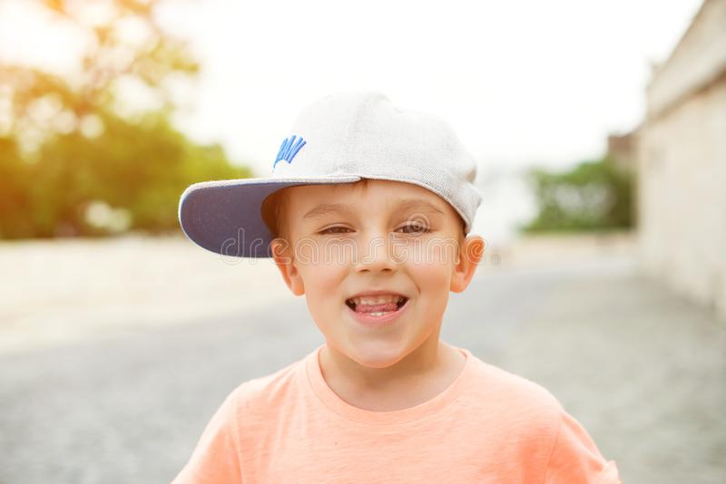 Cute little boy outdoors portrait. Funny child in a stylish cap. Smiling boy walking in city. Children style and fashion. Summer royalty free stock image