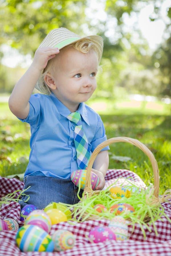 Cute Little Boy Outside Holding Easter Eggs Tips His Hat. Cute Little Boy Outside On Picnic Blanket Holding Easter Eggs Tips His Hat royalty free stock photos