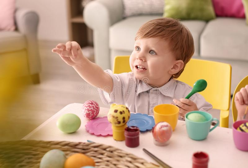 Cute little boy painting Easter eggs at table royalty free stock image