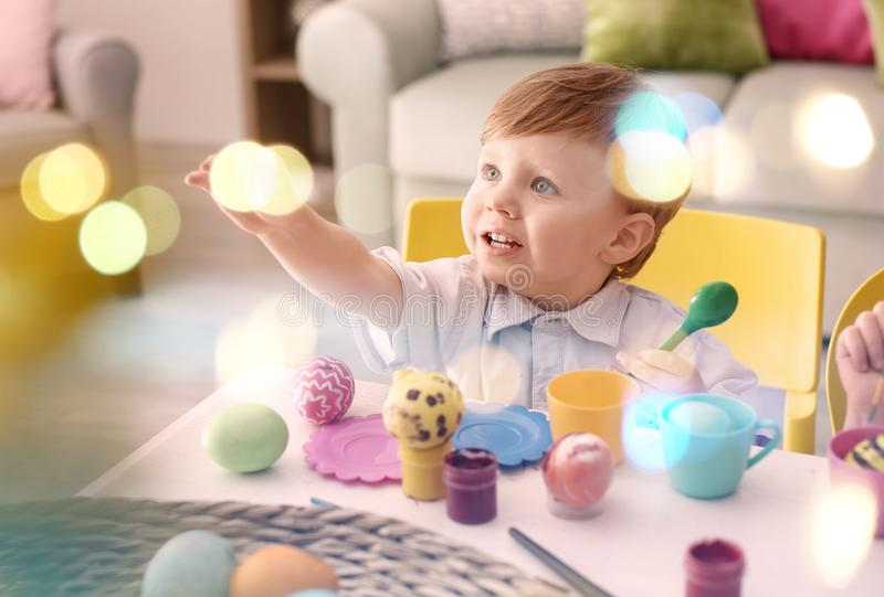 Cute little boy painting Easter eggs at table stock photo