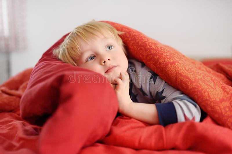 Cute little boy in pajamas having fun in bed after sleeping and watching TV or dreaming stock photo