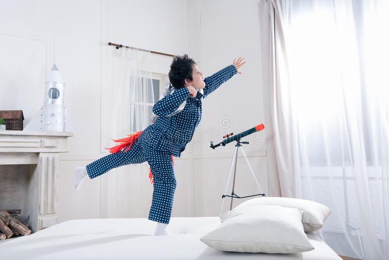 Cute little boy in pajamas playing astronaut on bed stock image