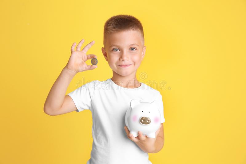 Cute little boy with piggy bank. On color background stock photo