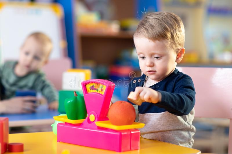 Cute little boy playing with abacus in nursery. Preschooler having fun with educational toy in daycare or creche. Smart stock photo