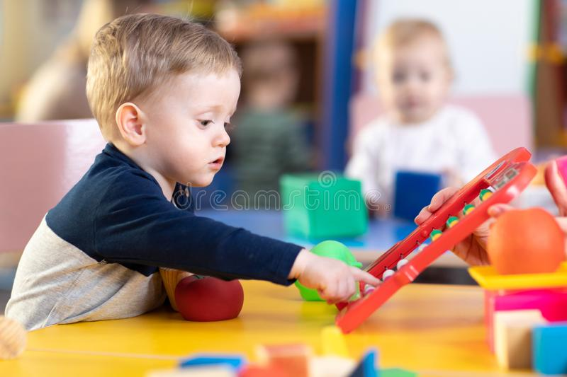 Cute little boy playing with abacus in nursery. Preschooler having fun with educational toy in daycare or kindergarten. Cute little kid boy playing with abacus royalty free stock photo