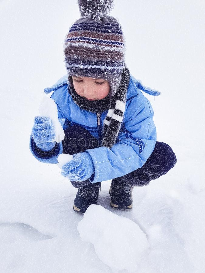 Cute little boy playing alone in the snow with snowballs royalty free stock photos