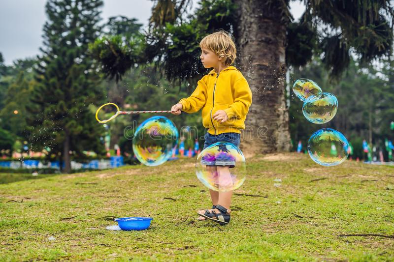 Cute little boy is playing with big bubbles outdoor royalty free stock photography