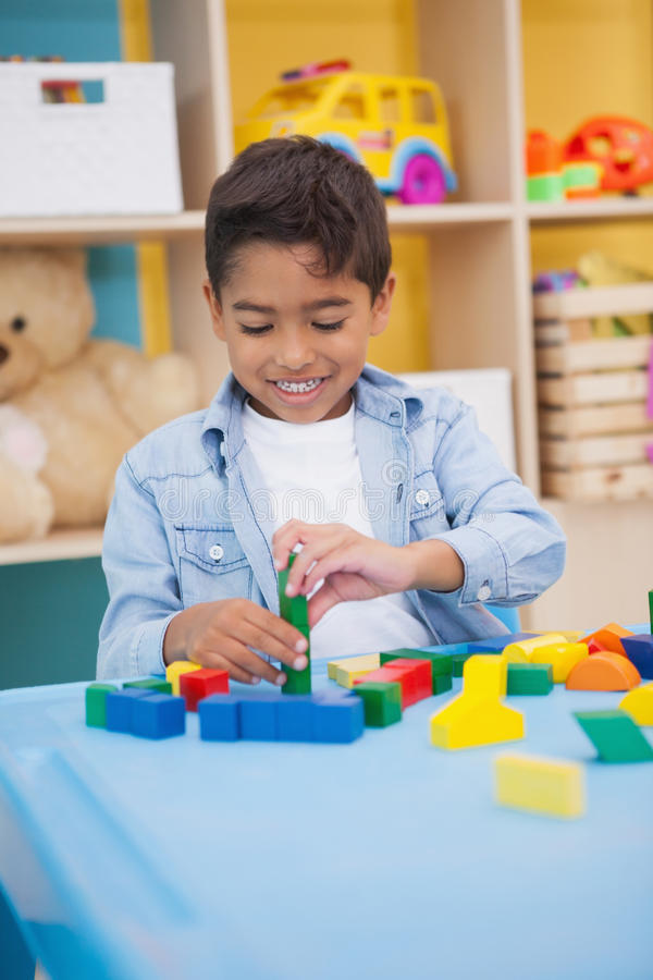 Cute little boy playing with building blocks. At the nursery school royalty free stock image