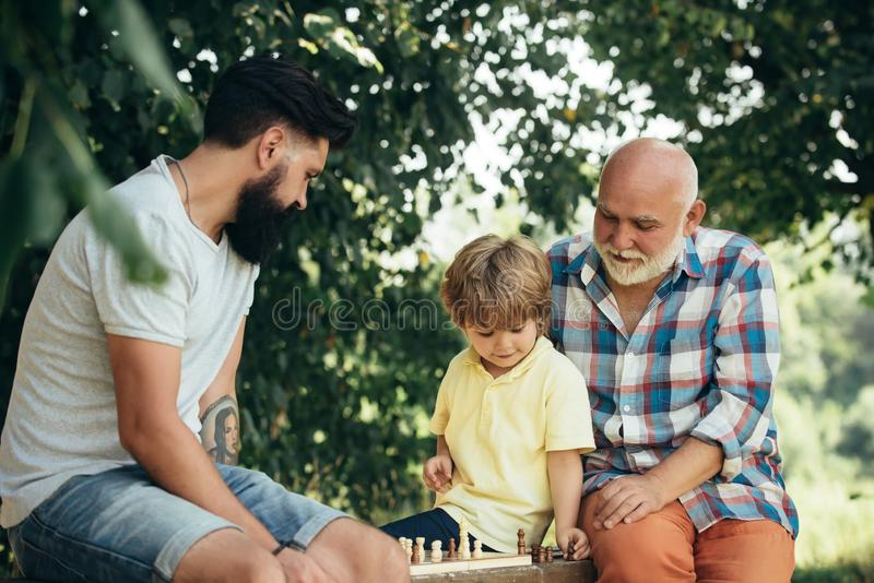 Cute little boy playing chess with Parents. Three different generations ages: grandfather father and son together. stock photo