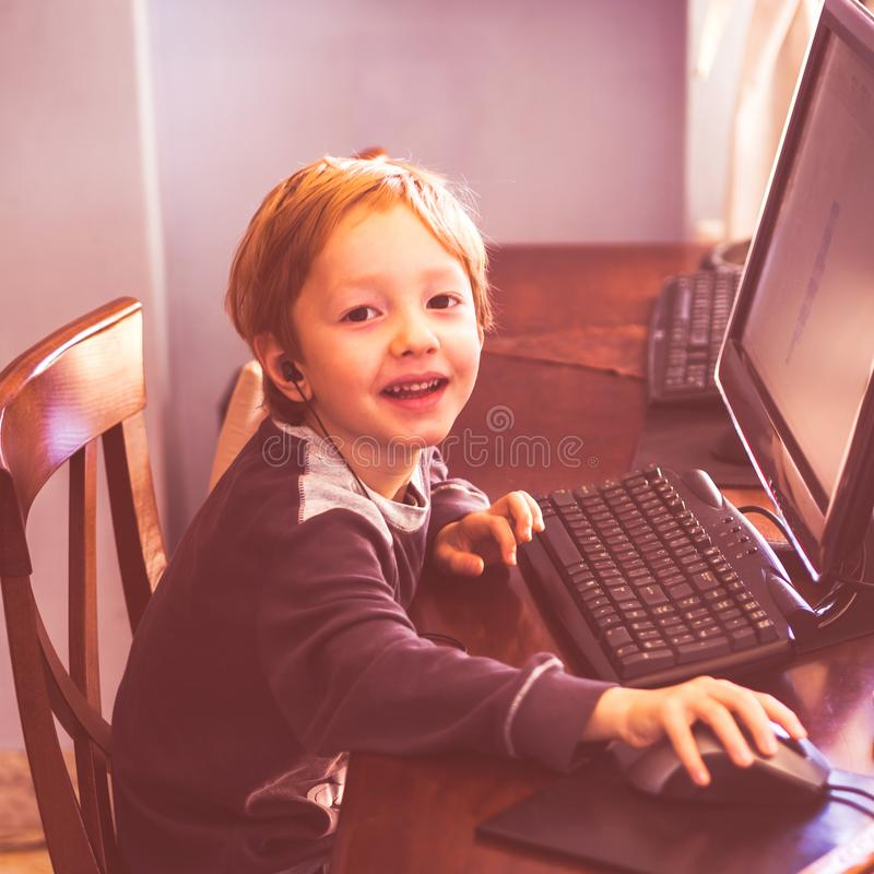 Cute little boy playing at computer with headset royalty free stock photos