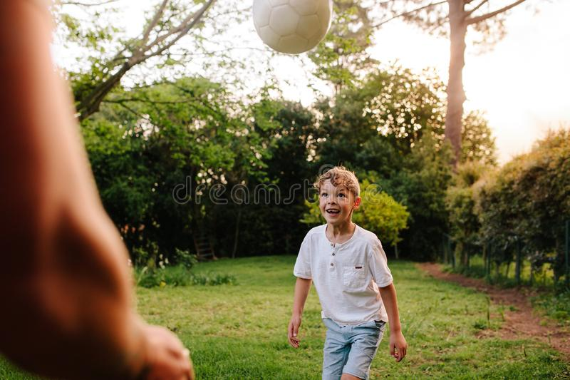Cute little boy playing football with his father royalty free stock images
