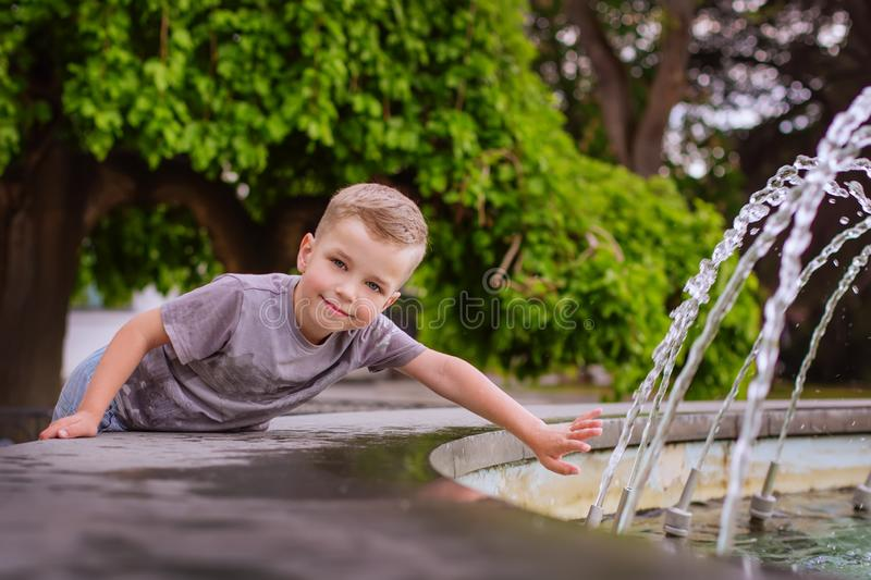Cute little boy playing with a fountain royalty free stock photography